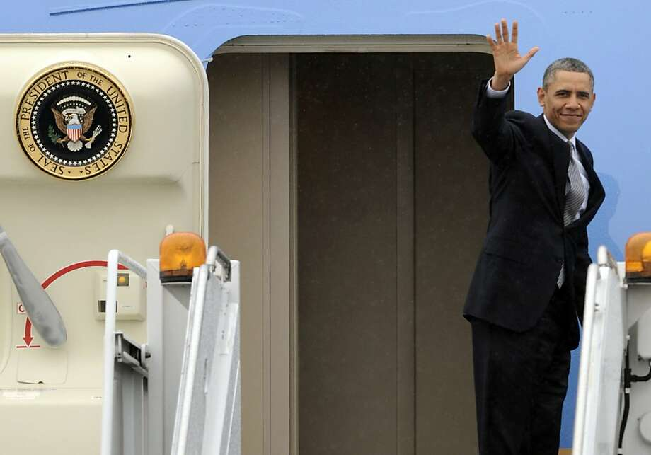 President Barack Obama waves while boarding Air Force One before leaving O'Hare International Airport in Chicago, Friday, March 15, 2013. (AP Photo/Paul Beaty) Photo: Paul Beaty, Associated Press