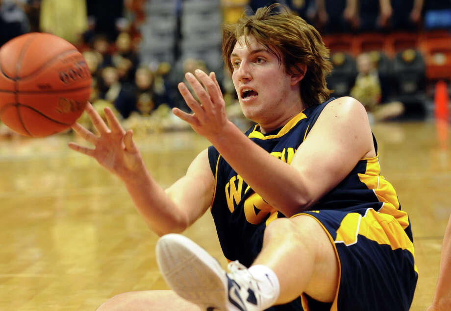 After falling to recover the basketbal Weston's #42 Grant Limone pass the ball to a teammate, during Class M boys basketball final action against Valley Regional at the Mohegan Sun Arena in Uncasville, Conn. on Friday March 15, 2013. Photo: Christian Abraham / Connecticut Post