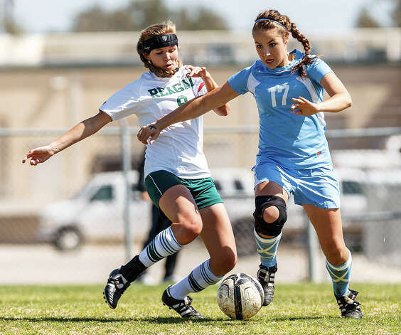 Johnson's Alyssa Clark (right) fights for the ball with Reagan's Ashley Crabbe during the first half of their District 26-5A girls soccer game at Blossom Athletic Center on Friday, March 15, 2013. Neither team was able to score and the game ended in a 0-0 tie.   MARVIN PFEIFFER/ mpfeiffer@express-news.net Photo: MARVIN PFEIFFER, Express-News / Express-News 2013