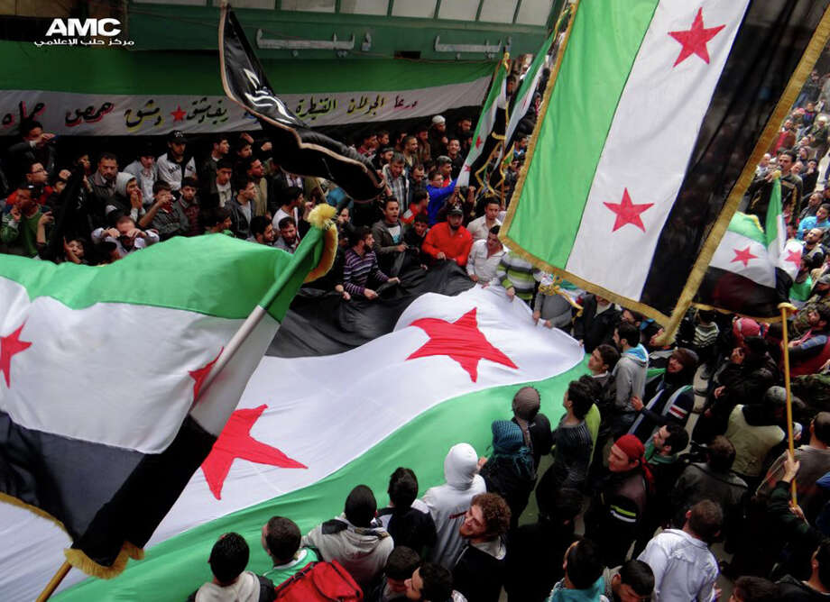 "In this citizen journalism image provided by Aleppo Media Center AMC which has been authenticated based on its contents and other AP reporting, anti-Syrian regime protesters, wave the Syrian revolutionary flags during a protest to mark the second anniversary of the their uprising, in Aleppo, Syria, Friday March 15, 2013. The chief of Syria's main, western-backed rebel group marked the second anniversary of the start of the uprising against President Bashar Assad on Friday by pledging to fight until the ""criminal"" regime is gone. (AP Photo/Aleppo Media Center, AMC) Photo: HOEP"