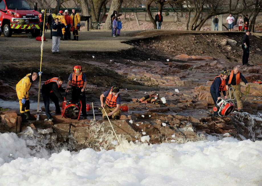 Rescuers search the Big Sioux River for two adults who went underwater after rescuing a boy who had fallen into the strong current, authorities said, Thursday, March 14, 2013 in Sioux Falls, S.D. (AP Photo/The Argus Leader, Elisha Page)  NO SALES Photo: Elisha Page