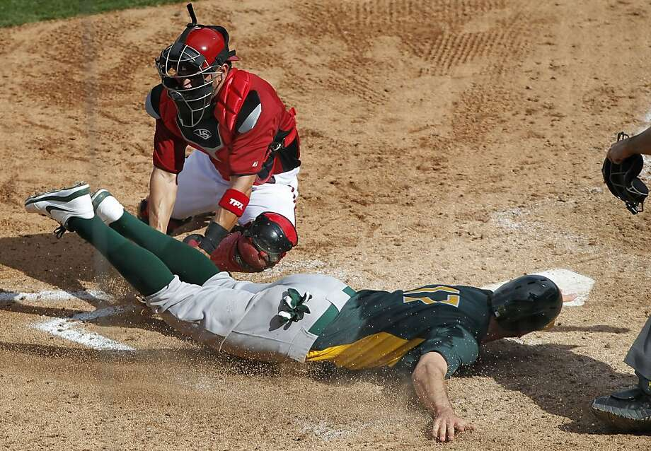 Diamondbacks catcher Wil Nieves makes the tag on Adam Rosales, making a headfirst slide a la Rickey Henderson, who's been working with the A's on baserunning. Henderson compares his style to the airplane that safely landed on the Hudson River. Photo: Michael Macor, The Chronicle