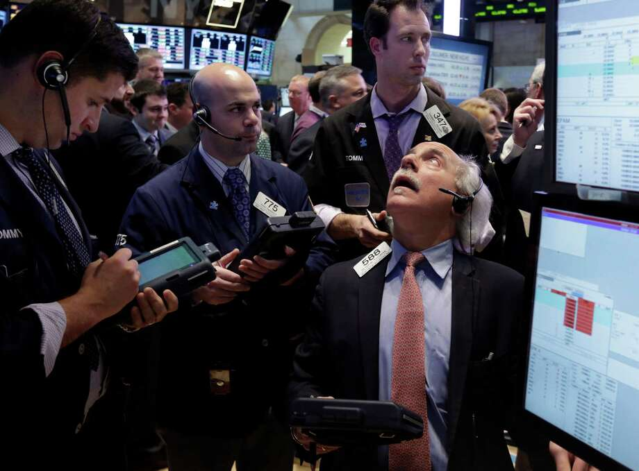 Peter Tuchman, right, works with fellow traders on the floor of the New York Stock Exchange Friday, March 15, 2013. U.S. stocks fell, ending the longest winning streak for the Dow Jones industrial average in nearly 17 years.  (AP Photo/Richard Drew) Photo: Richard Drew