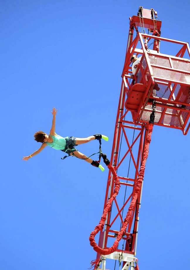 "Marissa Jimenez, 18, of Houston, makes the 130 foot jump off of the Super Bungee Jump at the Houston Livestock Show and Rodeo Friday, March 15, 2013, in Houston. She said she ""held on, closed her eyes, and let goâ it was really exciting!"" Photo: Karen Warren, Houston Chronicle / © 2013 Houston Chronicle"