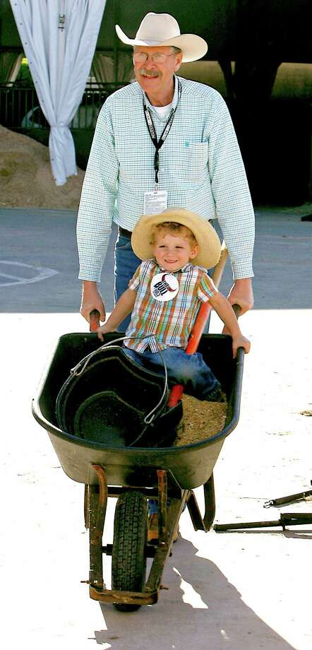 Bruce Prins, top, pushes his three-year-old grandson Owen Martin in a wheelbarrow near the stables for the grand entry parade and chuck wagon racing horses  prior to the start of RodeoHouston in Reliant Stadium Friday, March 15, 2013, in Houston. Photo: James Nielsen, Houston Chronicle / © 2013  Houston Chronicle