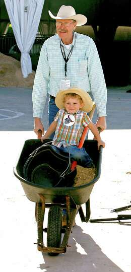 Bruce Prins, top, pushes his three-year-old grandson Owen Martin in a wheelbarrow near the stables f