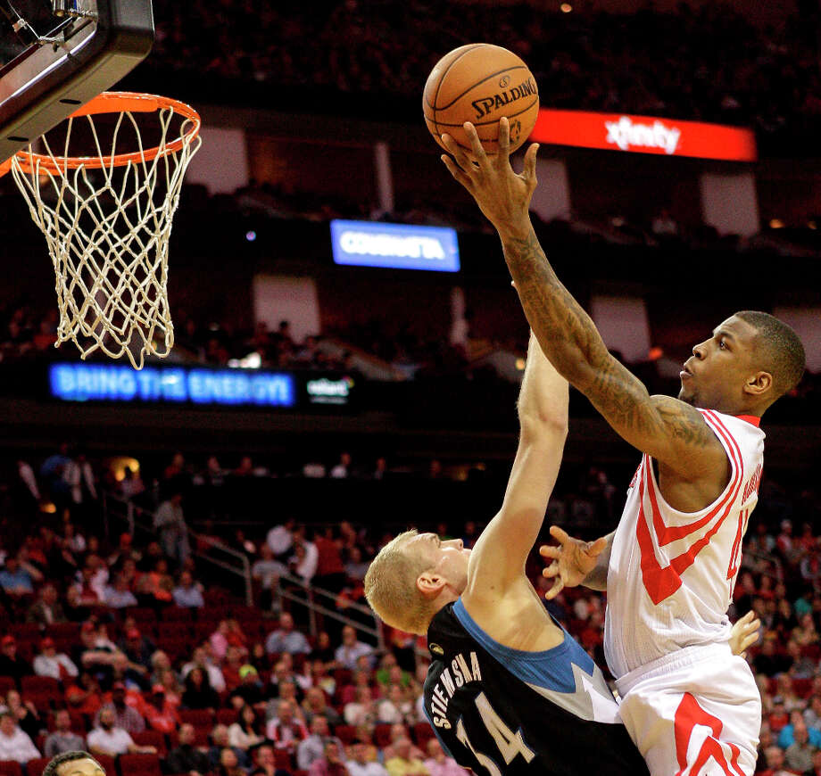 Rockets forward Thomas Robinson attempts a shot over Greg Stiemsma of the Timberwolves. Photo: Bob Levey / ©2013 Bob Levey