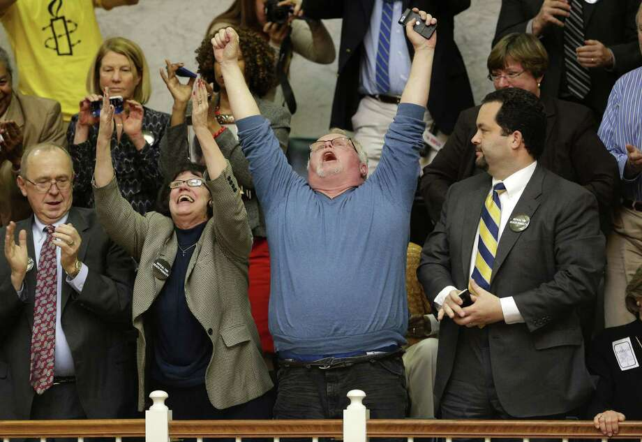 Kirk Bloodsworth, the first American sentenced to death who was exonerated by DNA, raises his arms after seeing Maryland lawmakers' vote to abolish capital punishment. He is flanked by supporters Sylvester Schieber (from left), Vicki Schieber and NAACP President Ben Jealous. Photo: Patrick Semansky / Associated Press