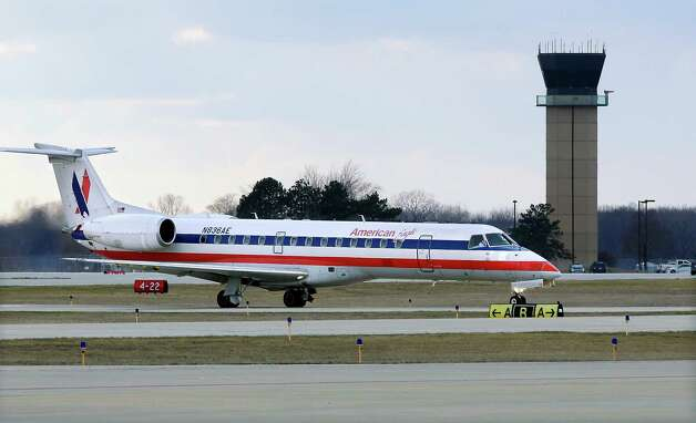 In this March 12, 2013 photo, an American Eagle jet taxis to a gate past the control tower after landing at the Abraham Lincoln Capital Airport in Springfield, Ill. The airport is one of nearly 240 small airports around the country that will likely shut down their air traffic control towers under federal budget cuts, stripping away a layer of safety during takeoffs and landings and leaving many pilots to manage the most critical stages of flight on their own. (AP Photo/Seth Perlman) Photo: Seth Perlman