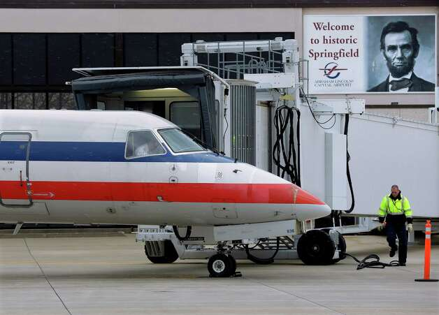 In this March 12, 2013 photo, a baggage handler walks by an American Eagle jet after it pulled up to a gate on arrival at the Abraham Lincoln Capital Airport in Springfield, Ill. The airport is one of nearly 240 small airports around the country that will likely shut down their air traffic control towers under federal budget cuts, stripping away a layer of safety during takeoffs and landings and leaving many pilots to manage the most critical stages of flight on their own. (AP Photo/Seth Perlman) Photo: Seth Perlman