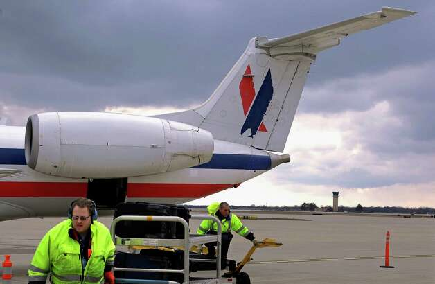 In this March 12, 2013 photo, baggage handlers unload an American Eagle jet after it landed at the Abraham Lincoln Capital Airport in Springfield, Ill. The airport is one of nearly 240 small airports around the country that will likely shut down their air traffic control towers under federal budget cuts, stripping away a layer of safety during takeoffs and landings and leaving many pilots to manage the most critical stages of flight on their own. (AP Photo/Seth Perlman) Photo: Seth Perlman
