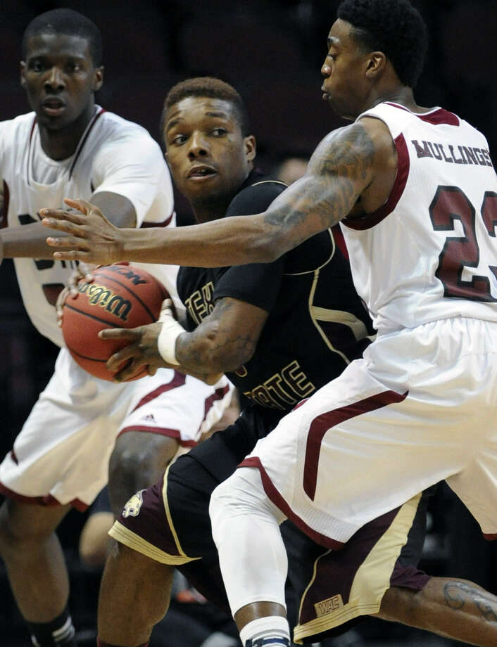 Texas State's Phil Hawkins (center) looks to pass as New Mexico State's Daniel Mullings defends. Photo: David Becker / Associated Press