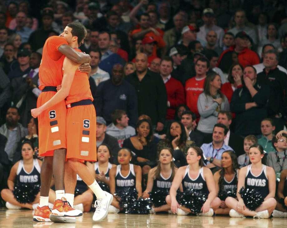 Baye Keita (left) and Michael Carter-Williams hug during the Orange's 58-55 overtime victory. Photo: Suzy Allman / New York Times