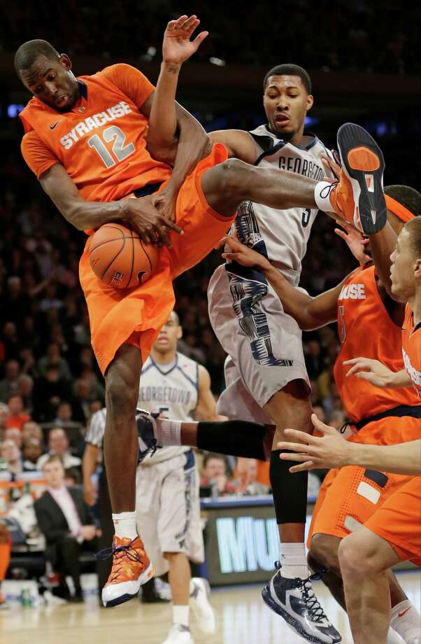 Syracuse's Baye Keita (12) and Georgetown's Mikael Hopkins (3) fight for control of the ball during the second half of an NCAA college basketball game at the Big East Conference tournament Friday, March 15, 2013, in New York. Syracuse won the game 58-55. (AP Photo/Frank Franklin II) Photo: Frank Franklin II