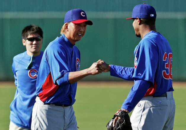 FILE - In this Feb. 12, 2013 file photo, Chicago Cubs' Kyuji Fujikawa, center, of Japan, gets a fist bump from teammate Edwin Jackson, right, as interpreter Ryo Shinkawa looks on during a spring training baseball workout  in Mesa, Ariz. A new rule in Major League Baseball that lets interpreters join managers and coaches on the mound when pitchers aren't fluent in English might still need some tweaking. The rule has already been used in spring training. (AP Photo/Ross D. Franklin, File) Photo: Ross D. Franklin
