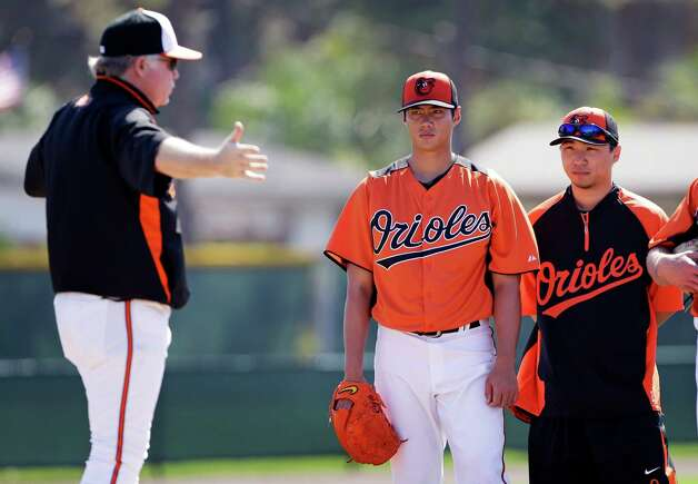 FILE - In this Feb. 13, 2013 file photo, Baltimore Orioles starting pitcher Wei-Yin Chen, center, listens to manager Buck Showalter, left, as interpreter Tim Lin, right, looks on during a baseball spring training workout  in Sarasota, Fla. A new rule in Major League Baseball that lets interpreters join managers and coaches on the mound when pitchers aren't fluent in English might still need some tweaking. The rule has already been used in spring training. (AP Photo/Charlie Neibergall, File) Photo: Charlie Neibergall