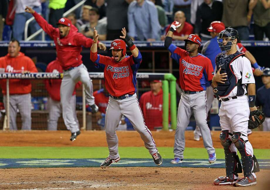 Puerto Rico's Mike Aviles (center) waves teammate Alex Rios home during Friday's night's 4-3 victory over the United States in the World Baseball Classic at Marlins Park in Miami. Photo: Mike Ehrmann / Getty Images