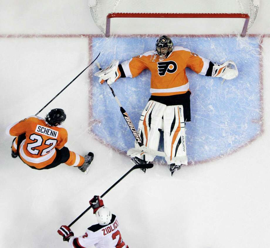 Flyers goalie Ilya Bryzgalov, top, blocks a shot by New Jersey's' Marek Zidlicky. Photo: Matt Slocum, STF / AP