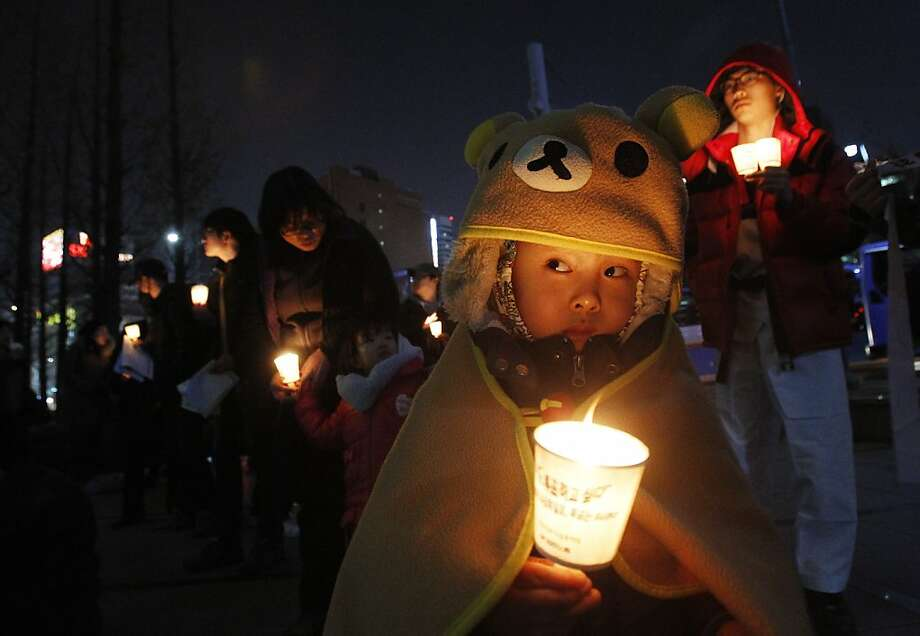 A South Korean child holds a candle light  during a rally denouncing the annual joint military exercises, dubbed Key Resolve and Foal Eagle, South Korea and the United States joint military exercise, in Seoul, South Korea, Friday, March 15, 2013. Pyongyang's most recent threats follow U.N. sanctions imposed last week over its third nuclear test, which it conducted Feb. 12. North Korea says ongoing annual U.S.-South Korean military drills are invasion rehearsals.(AP Photo/Ahn Young-joon) Photo: Ahn Young-joon, Associated Press