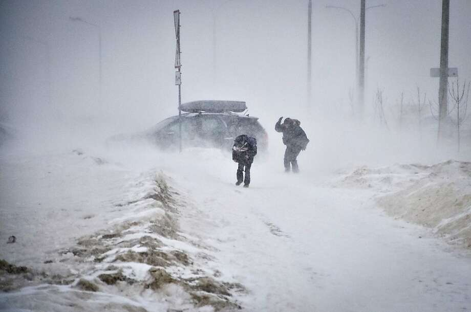 People struggle against wind and drifting snow in the Belarus capital Minsk, on March 15, 2013. A snow storm marched today across Minsk as the temperatures dropped to -6 C (21 F). ALEXEY GROMOV/AFP/Getty Images Photo: Alexey Gromov, AFP/Getty Images