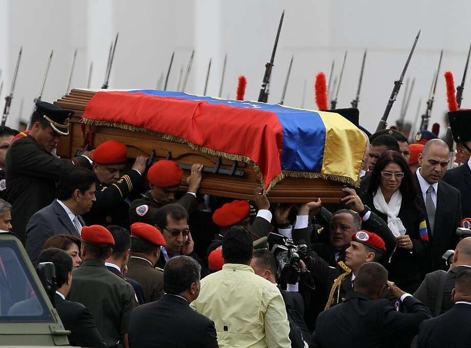 The coffin containing the remains of Venezuela's late President Hugo Chavez is carried from the military academy, at the start of a procession to the military museum, his final resting place, in Caracas, Venezuela, Friday, March 15, 2013. Venezuelans lined up to bid their last farewell to Hugo Chavez on Friday. Chavez was 58 when he died of an undisclosed type of cancer on March 5. (AP Photo/Fernando Llano) Photo: Fernando Llano, Associated Press