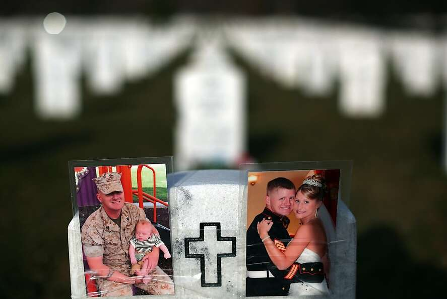 Photographs cover the top of the headstone at the grave of USMC Sgt. Christopher James Jacobs in Sec