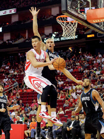 Rockets point guard Jeremy Lin looks to make a pass in midair. Photo: Bob Levey / ©2013 Bob Levey
