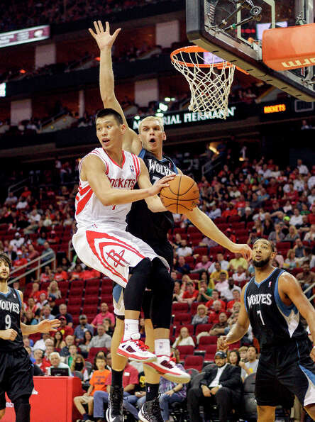 Rockets point guard Jeremy Lin looks to make a pass in midair.