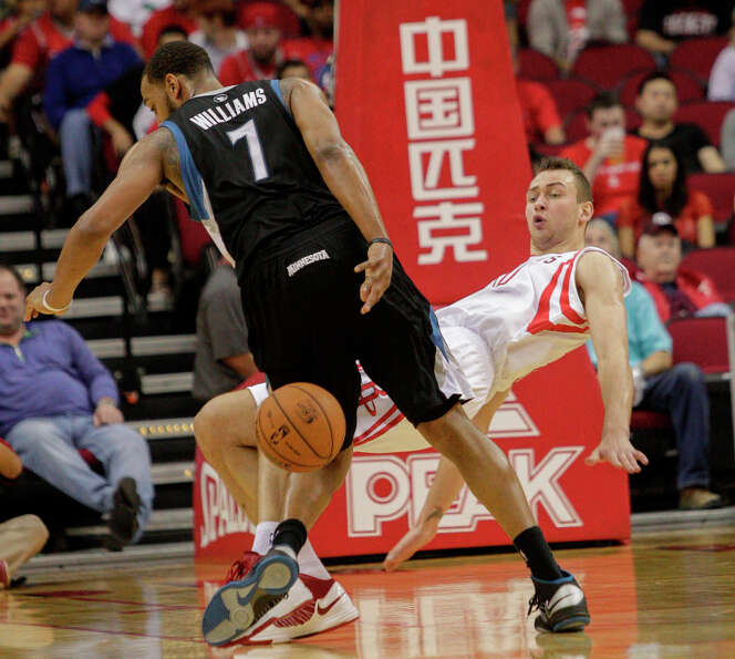 Rockets power forward Donatas Motiejunas takes a charge from Derrick Williams of the Timberwolves.
