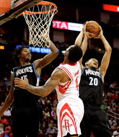 Timberwolves power forward Chris Johnson grabs a rebound away from Greg Smith of the Rockets. Photo: Bob Levey / ©2013 Bob Levey