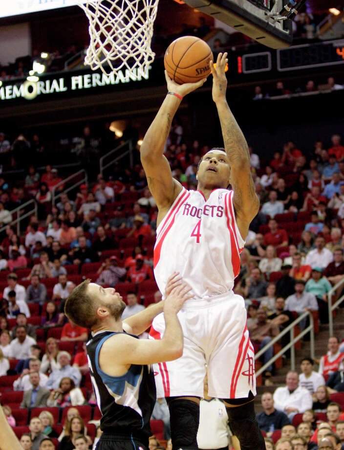Rockets forward Greg Smith attempts a shot over J.J. Barea of the Timberwolves. Photo: Bob Levey / ©2013 Bob Levey