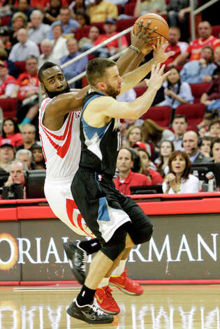 Rockets guard James Harden and J.J. Barea of the Timberwolves collide for a loose ball during the second half. Photo: Bob Levey / ©2013 Bob Levey