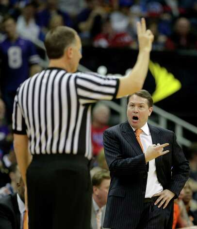 Oklahoma State head coach Travis Ford, right, argues with an official during the first half an NCAA college basketball game against Kansas State in the Big 12 men's tournament on Friday, March 15, 2013, in Kansas City, Mo. (AP Photo/Charlie Riedel) Photo: Charlie Riedel, Associated Press / AP