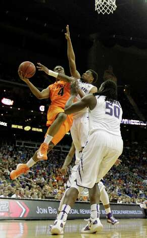 Oklahoma State guard/forward Brian Williams (4) gets past Kansas State guard Shane Southwell (1) and forward D.J. Johnson (50) to shoot during the first half an NCAA college basketball game in the Big 12 men's tournament on Friday, March 15, 2013, in Kansas City, Mo. (AP Photo/Charlie Riedel) Photo: Charlie Riedel, Associated Press / AP