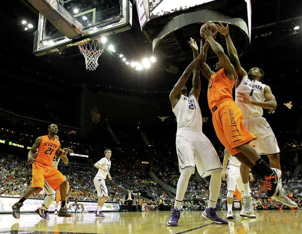 Oklahoma State guard/forward Le'Bryan Nash (2) is pressured by Kansas State forward Jordan Henriquez (21) and guard Shane Southwell (1) while shooting during the first half an NCAA college basketball game in the Big 12 men's tournament on Friday, March 15, 2013, in Kansas City, Mo. (AP Photo/Charlie Riedel) Photo: Charlie Riedel, Associated Press / AP