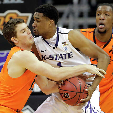 Oklahoma State guard Christien Sager, left, and Kansas State guard Shane Southwell (1) fight over a ball during the first half an NCAA college basketball game in the Big 12 men's tournament on Friday, March 15, 2013, in Kansas City, Mo. (AP Photo/Charlie Riedel) Photo: Charlie Riedel, Associated Press / AP