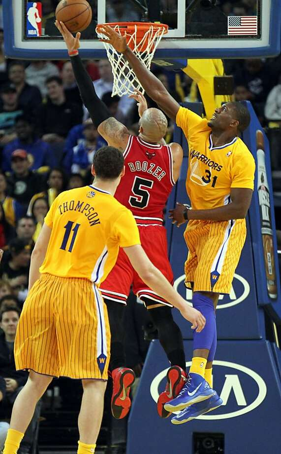 The Bulls' Carlos Boozer scores despite the effort of Warriors center Festus Ezeli (31). Photo: Lance Iversen, The Chronicle