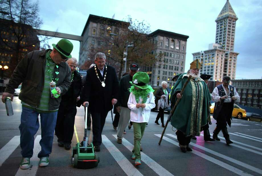 """Participants march during the annual """"Laying o' the Green Stripe"""" along Fourth Avenue in downtown Seattle on Friday, March 15, 2013. The event is a mini-parade in which a stripe is painted on the street to mark the route of the St. Patrick's Day Parade. At Westlake Park, the group painted a large shamrock with non-permanent paint and held a traditional Irish folk dance. Photo: JOSHUA TRUJILLO / SEATTLEPI.COM"""