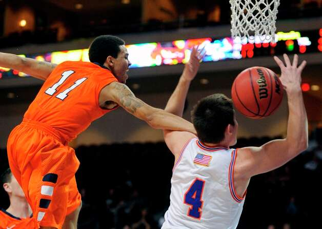 UT Arlington's Drew Charles (4) is fouled by UTSA's Michael Hale III (11) as he was taking a shot during the first half of a Western Athletic Conference tournament NCAA college basketball game, Friday, March 15, 2013 in Las Vegas. Photo: David Becker, Associated Press / FR170737 AP