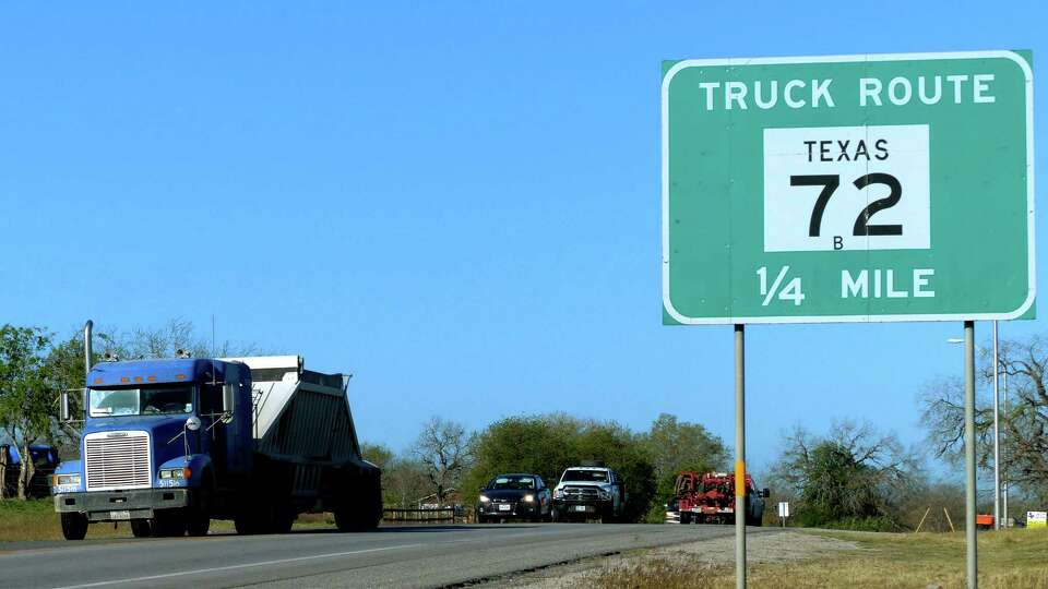 Truck traffic related to the Eagle Ford Shale energy boom travels on Texas 72 near Kenedy, Texas, on