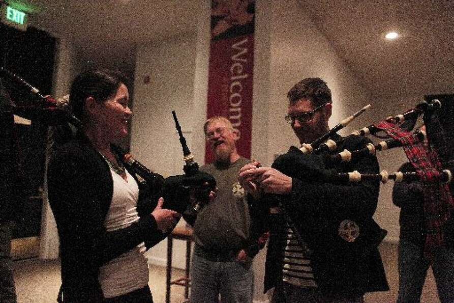 Isabel Stenzel gets her bagpipes tuned with the help of her bandmates in the Stewart Tartan Pipes an