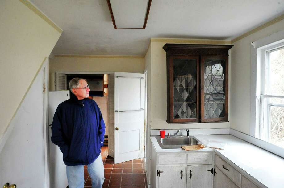 Paul McIlvaine looks at the town-owned cottage on the property up for auction in the Brookfield historic zone Saturday, March 16, 2013 in Conn. Photo: Michael Duffy / The News-Times