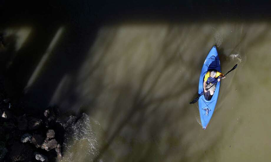 A boater paddles under a bridge  during the Buffalo Bayou Regatta  Saturday, March 16, 2013 in Houston. At least 500 boats are participating in the 15 mile race. Photo: Melissa Phillip, Houston Chronicle / © 2013  Houston Chronicle