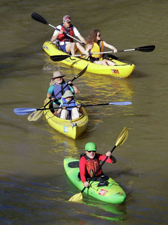 People paddle along during the Buffalo Bayou Regatta  Saturday, March 16, 2013 in Houston. At least 500 boats are participating in the 15 mile race. Photo: Melissa Phillip, Houston Chronicle / © 2013  Houston Chronicle