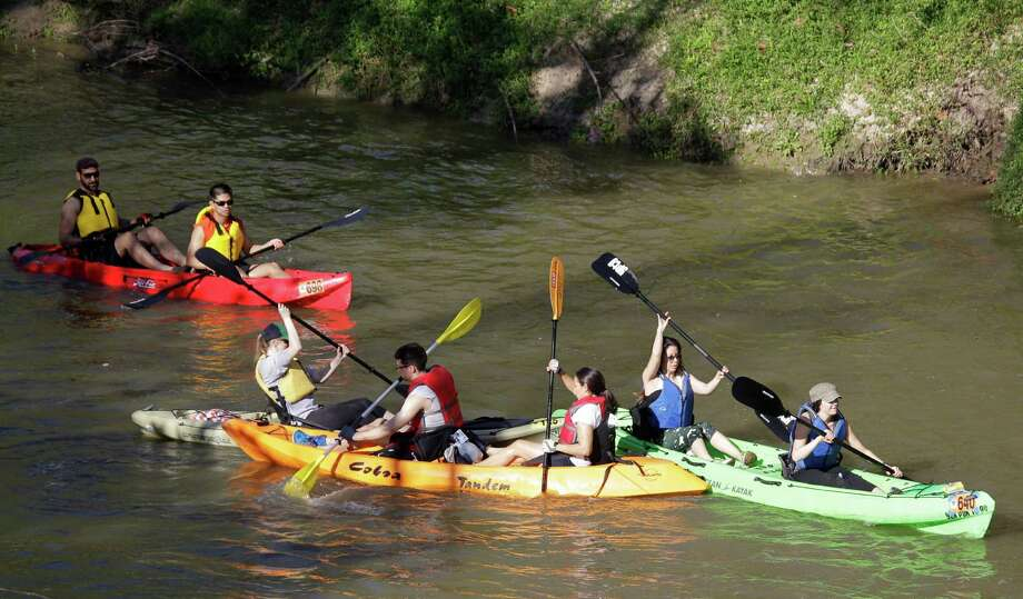 A couple tries to find the direction as people paddle along during the Buffalo Bayou Regatta  Saturday, March 16, 2013 in Houston. At least 500 boats are participating in the 15 mile race. Photo: Melissa Phillip, Houston Chronicle / © 2013  Houston Chronicle