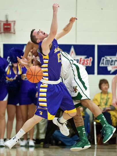 Vermont's Trey Blue, rear, fouls Albany's Peter Hooley during an NCAA college basketball game in the