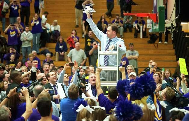 Albany coach Will Brown, top, holds up the in celebration after they defeated Vermont 53-49 in an NCAA college basketball game in the championship of the America East Conference tournament in Burlington, Vt. on Saturday, March 16, 2013. Photo: Glenn Russell, Glenn Russell / AP Photo/The Burlington Free Press / The Burlington Free Press