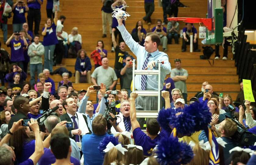 Albany coach Will Brown, top, holds up the in celebration after they defeated Vermont 53-49 in an NC