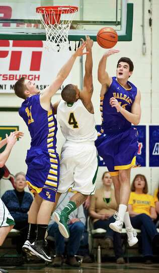 Vermont's Trey Blue (4) has a shot knocked away by Albany's John Puk, right, as Luke Devlin looks on