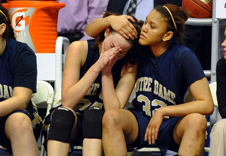 Notre Dame of Fairfield #32 Briana Mann, right comforts teammate #24 Aly Furgiuele in the final minutes of Class M girls basketball final action against Cromwell at the Mohegan Sun Arena in Uncasville, Conn. on Friday March 15, 2013. Cromwell beat ND Fairfield 42-28.
